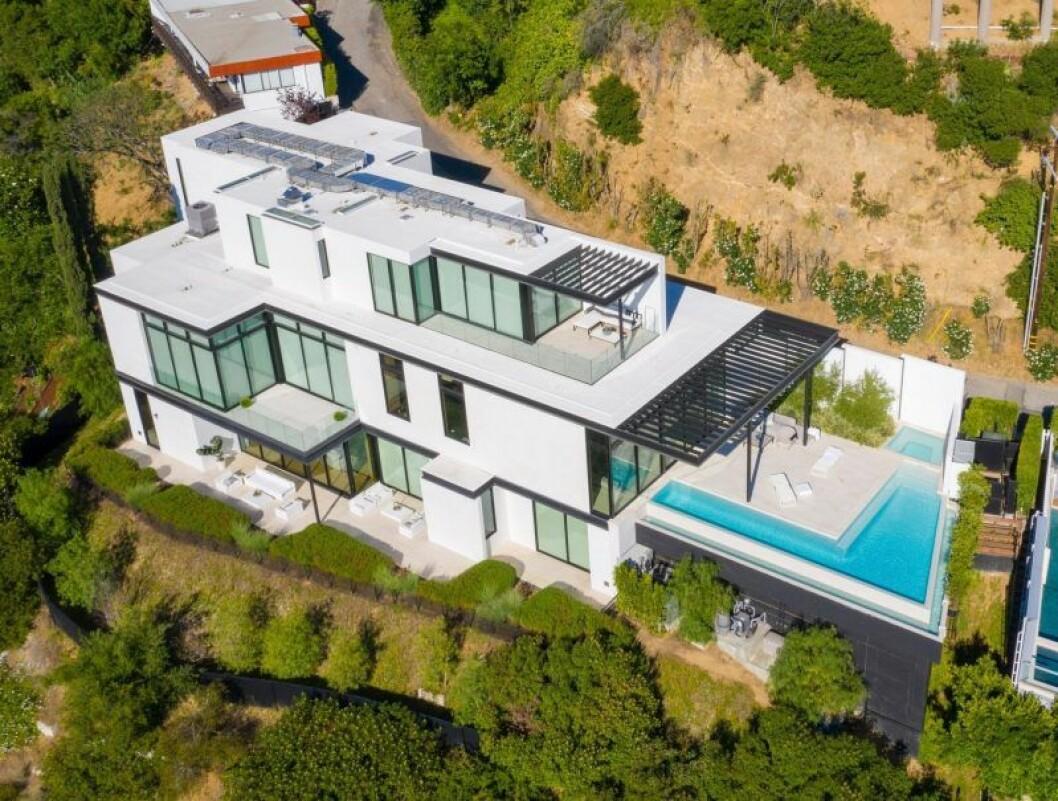ett stort hus i vitt och glas med en pool utanför.