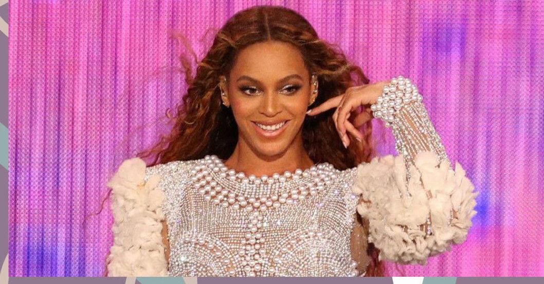 Beyoncé ler i vit pärlklänning mot en rosa bakgrund