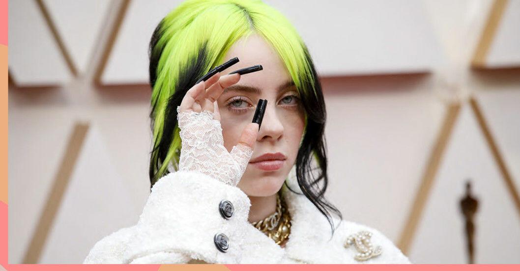 Billie Eilish med grönt och svart hår, vit jacka från chanel och långa svarta naglar som hon håller mot ansiktet