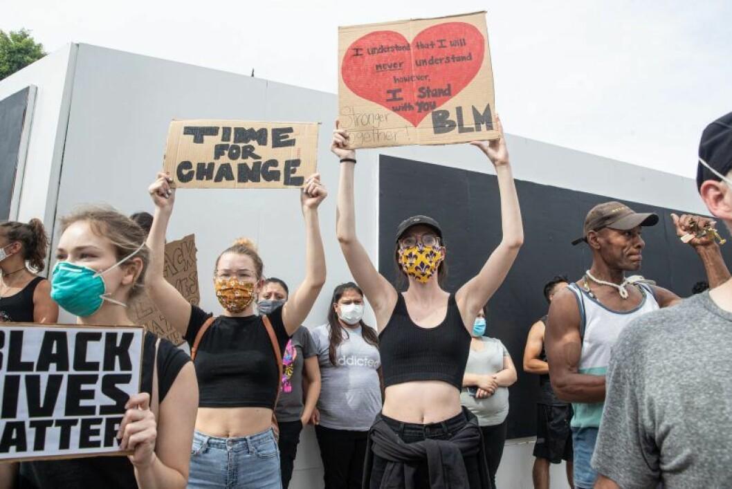 Tjejer håller upp skyltar med budskap om Black Lives Matter