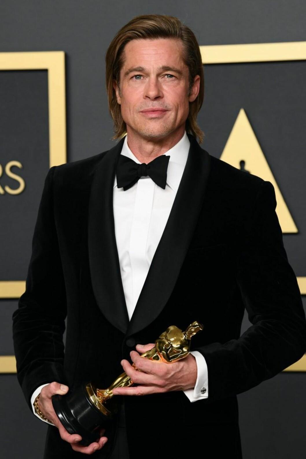 Brad Pitt I smoking håller i en statyett.