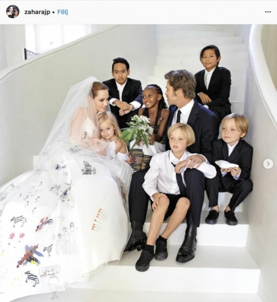 Brad Pitt och Angelina Jolie sitter i en vit trapp med alla sina barn och Angelina Jolie har en brudklänning på sig