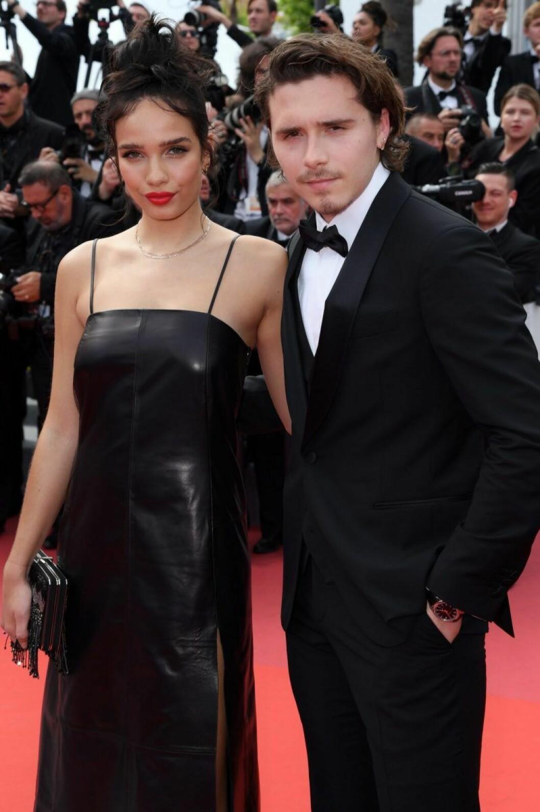 Brooklyn Beckham i svart kostym och Hana Cross i svart klänning på röda mattan