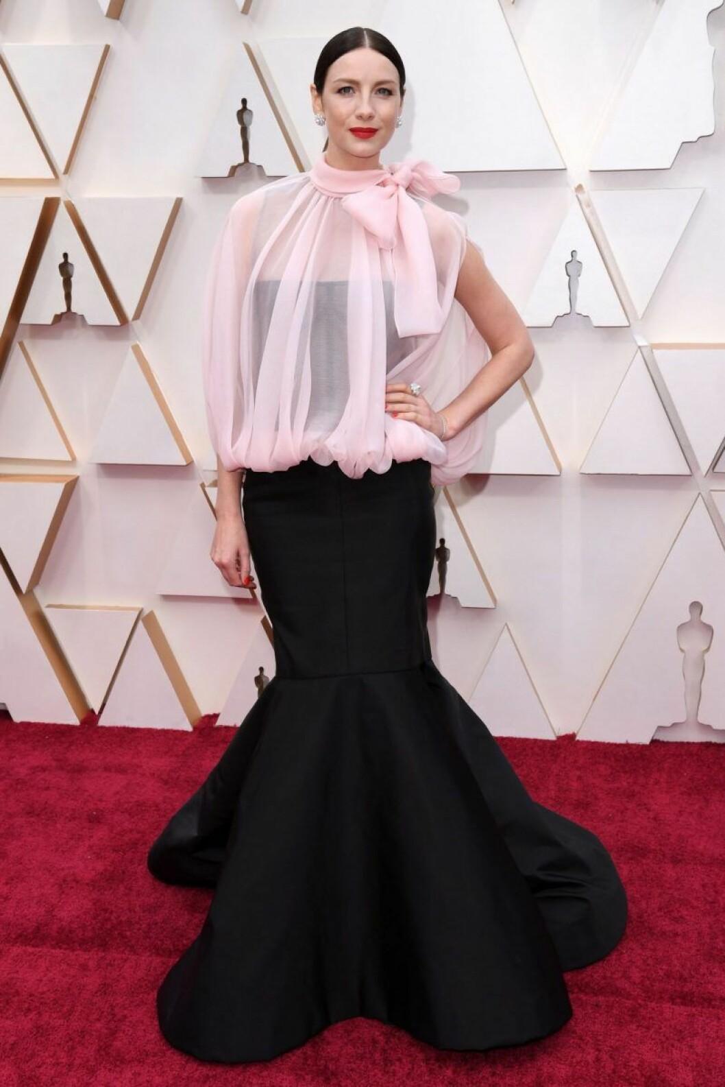 Caitriona Balfe i svart och rosa klänning på röda mattan