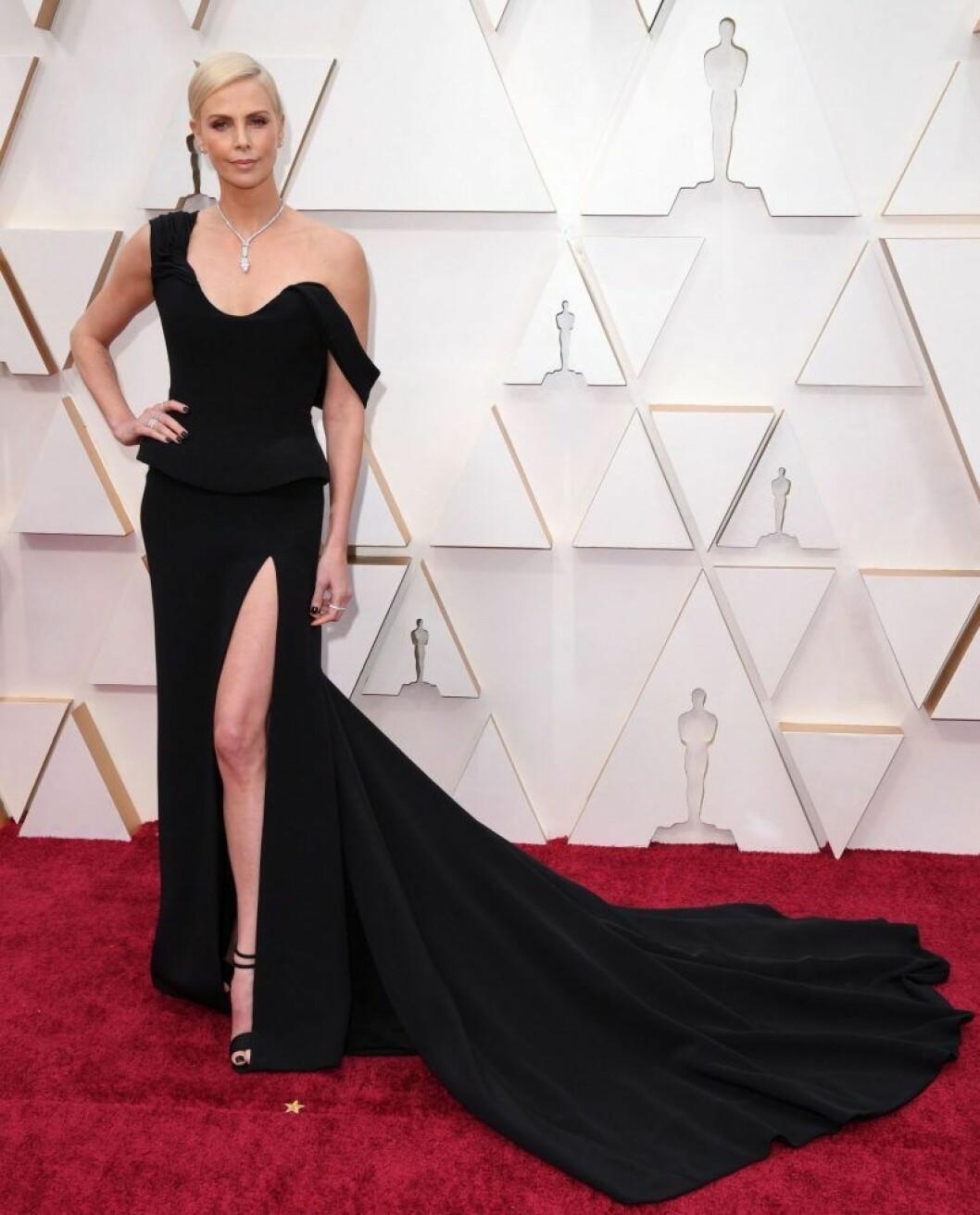 Charlize Theron i svart klänning på röda mattan.