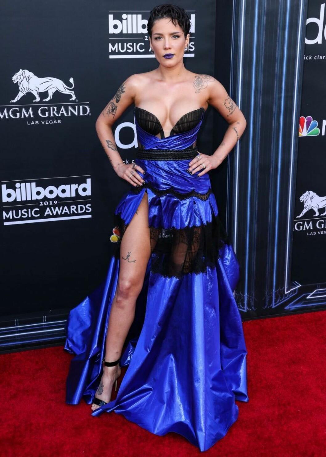Halsey i en blå och svart klänning och kort svart hår och blått läppstift