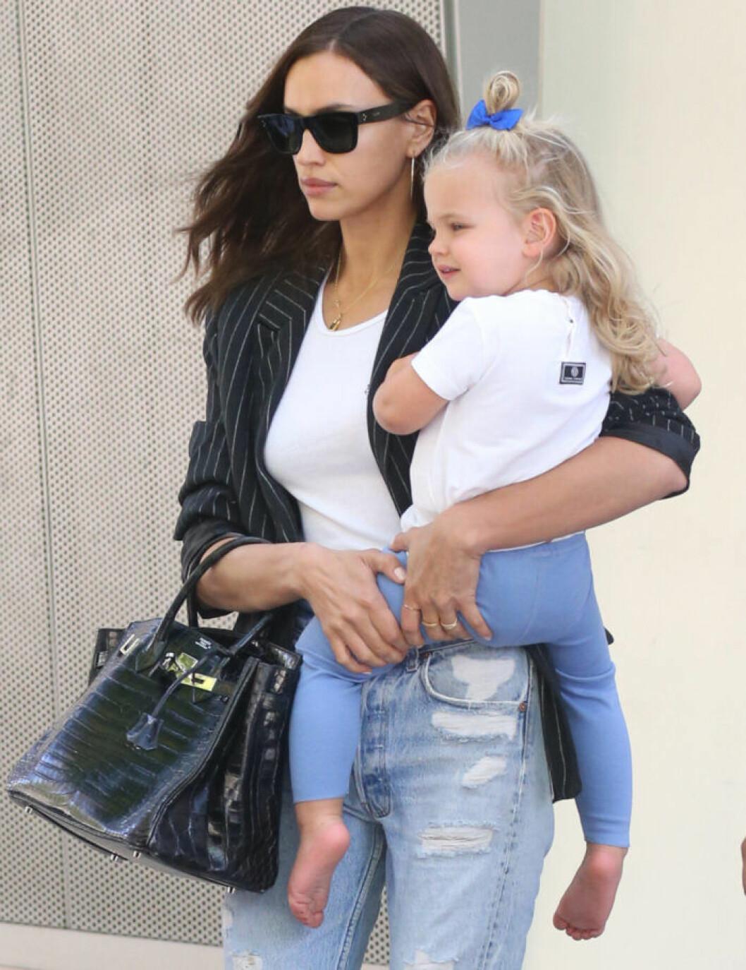 Irina Shayk har jeans, vit t-shirt och svart kavaj och bär sin dotter på höften