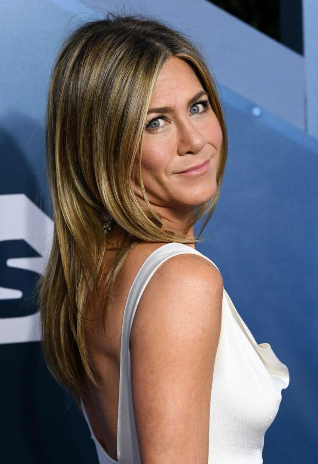 Jennifer Aniston tittar över axeln och ler