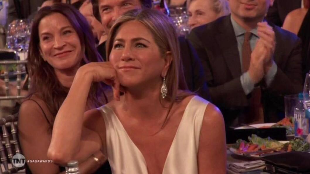 Jennifer Aniston lutar huvudet i sin ena hand och ler