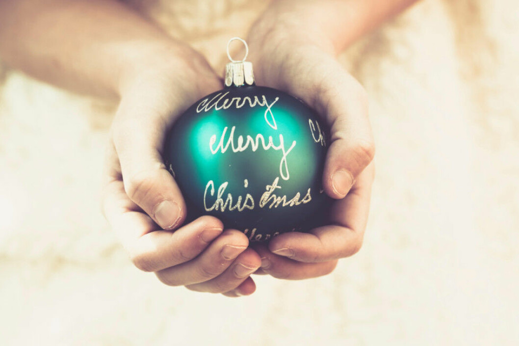 Girl's hands holding green Christmas bauble with the words 'Merry Christmas'