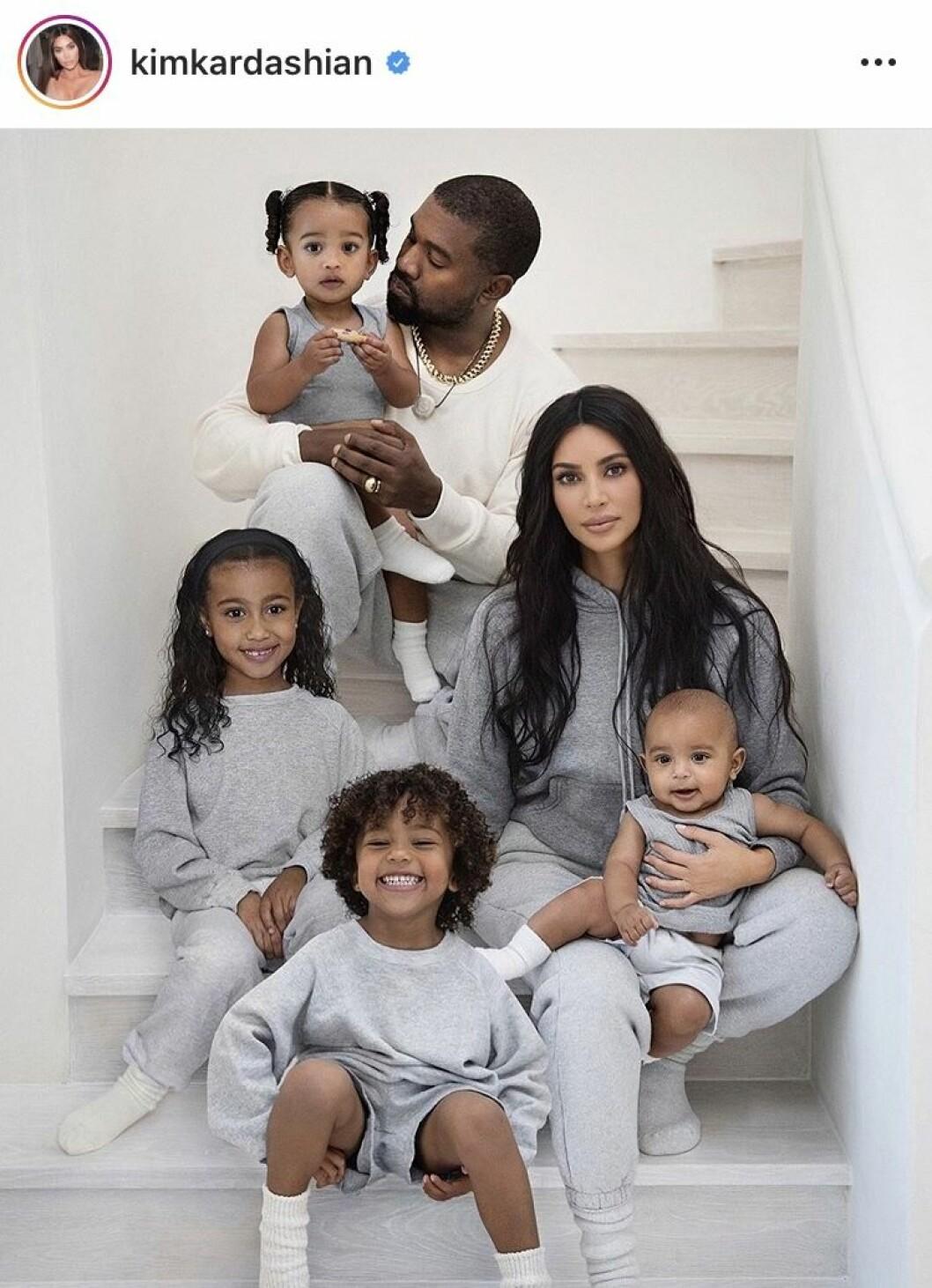 Kim Kardashian och Kanye West sitter i en trappa med alla sina barn och alla har grå mjukiskläder