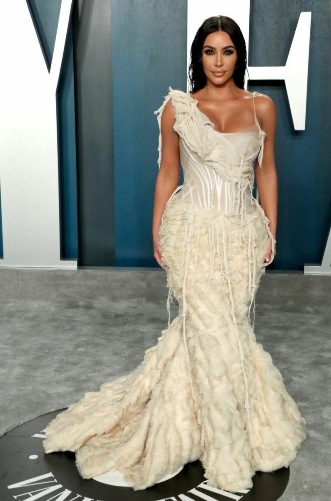 Kim Kardashian West i vit klänning med fjädrar