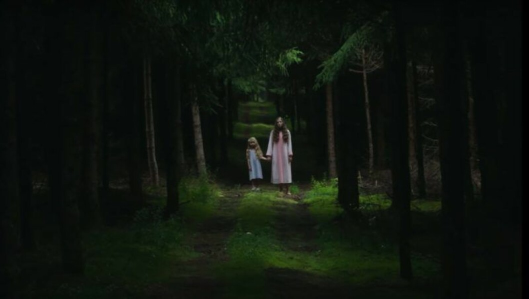 Två flickor står i en mörk skog och håller handen i zombiefilmen Les Affamés som finns på Netflix.