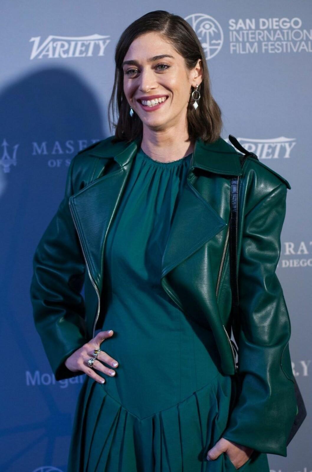 Lizzy Caplan i grön skinnjacka och grön klänning