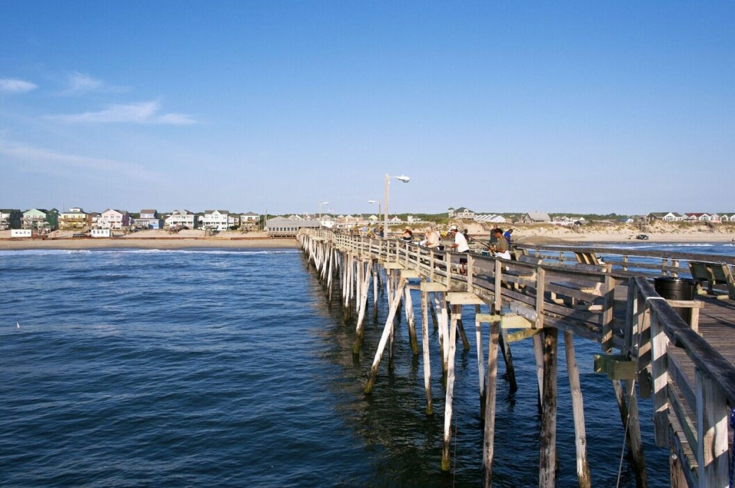 En lång fiskepir i vattnet där folk står och fiskar