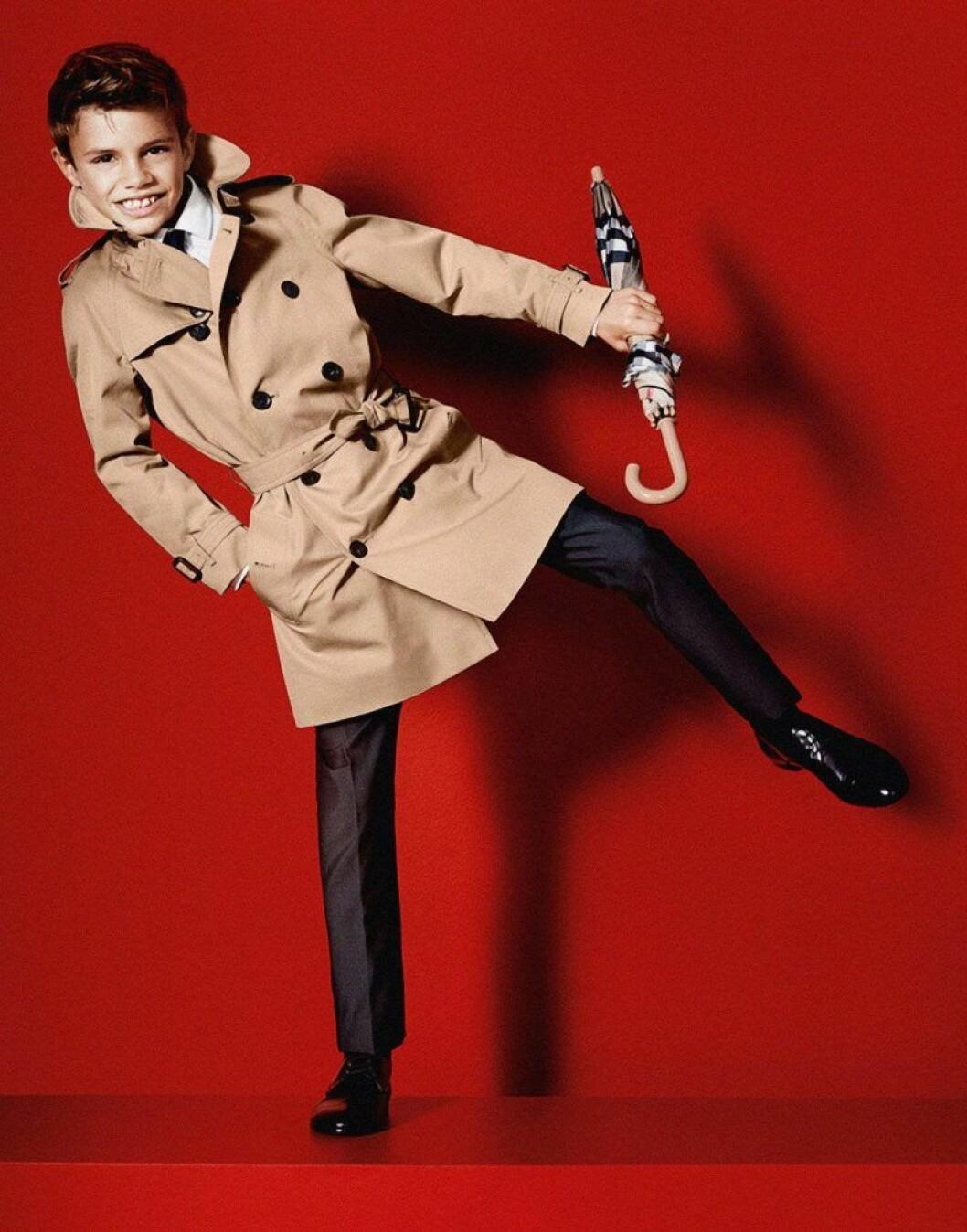 Romeo Beckham i beige kappa och paraply framför en röd bakgrund