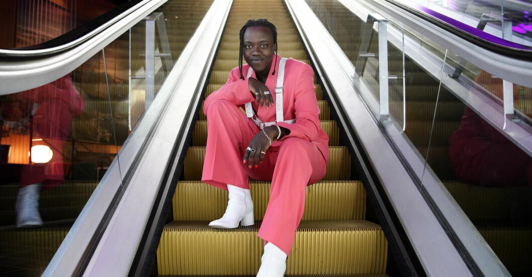 Tusse Chiza i en rosa kostym och vita klackar. Ler mot kameran.
