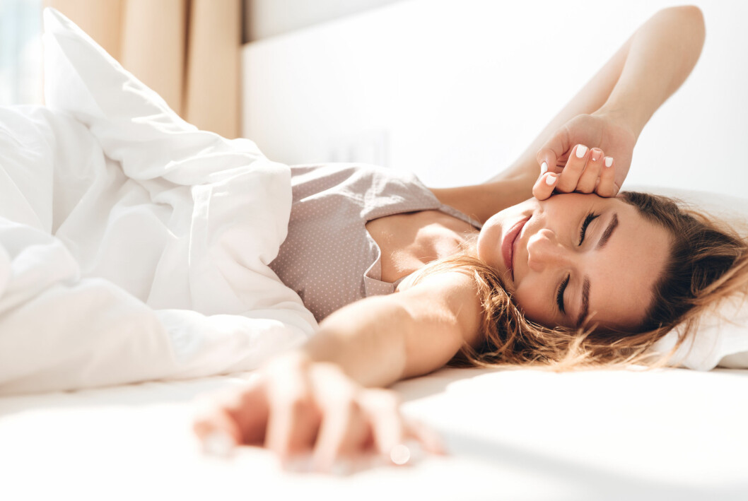 Kvinna som njuter i sängen