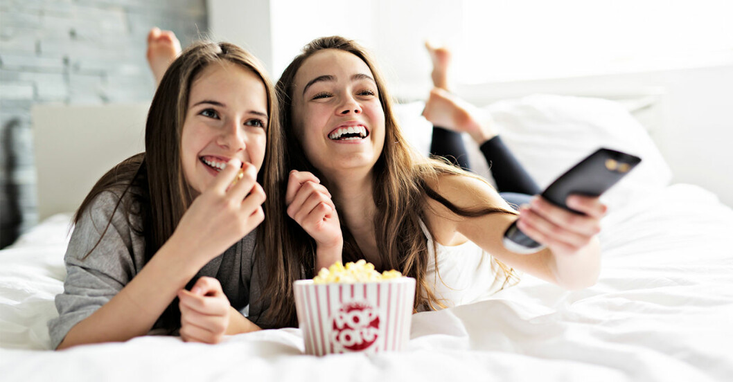 Systrar ligger i sängen och äter popcorn